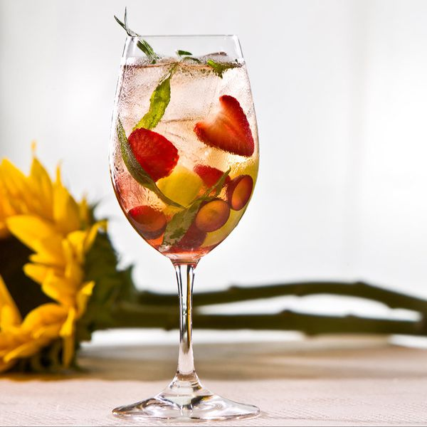 front porch swing cocktail in a wine glass with berries and herbs