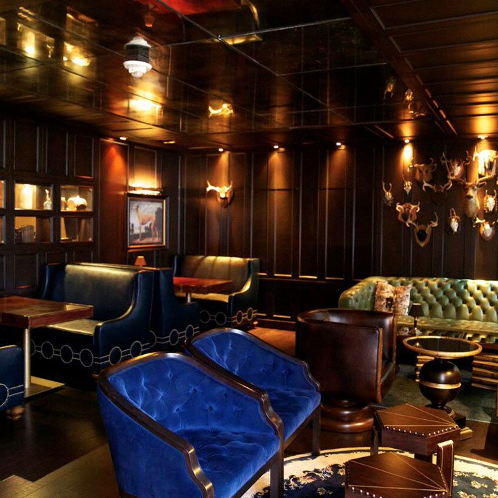Library Bar interior with a bright blue upholstered pair of love seats and dark wood paneled walls