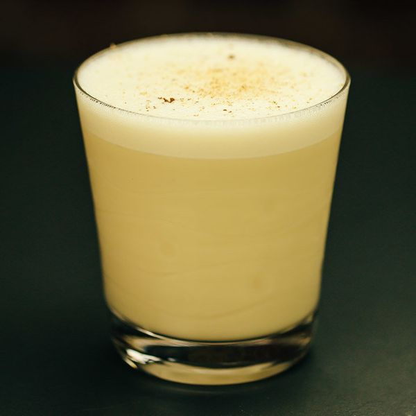 bourbon milk punch with frothy head and freshly grated nutmeg on top
