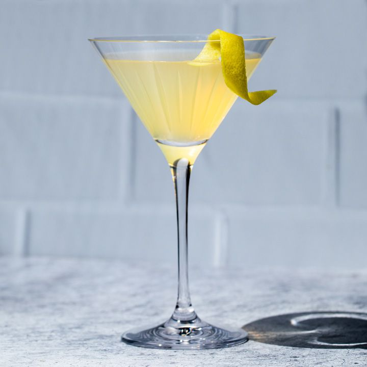 Tequila Martini with a lemon twist, set against a white tile background