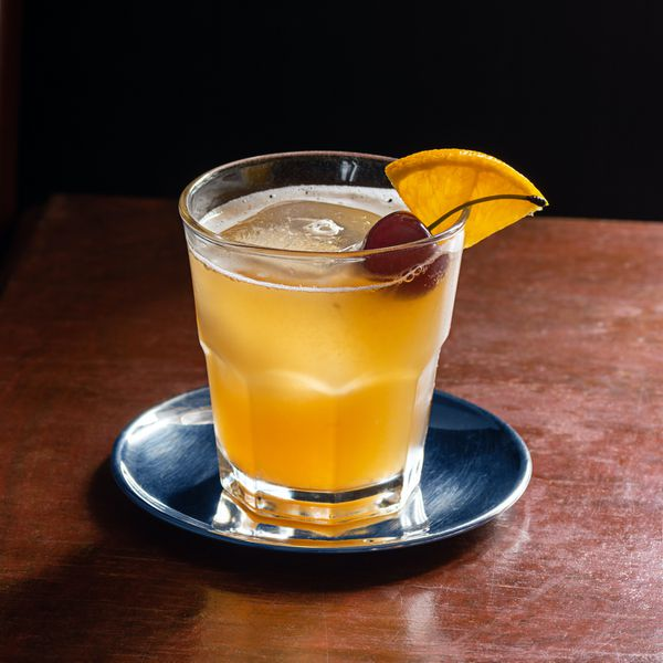 An Amaretto Sour cocktail on the rocks with a cherry and orange slice garnish on a dark wood table.