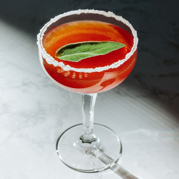 A bright orange-red cocktail served in a coupe glass with a sugared rim and a single sage leaf as its garnish; the glass is shot from above on a white marble surface