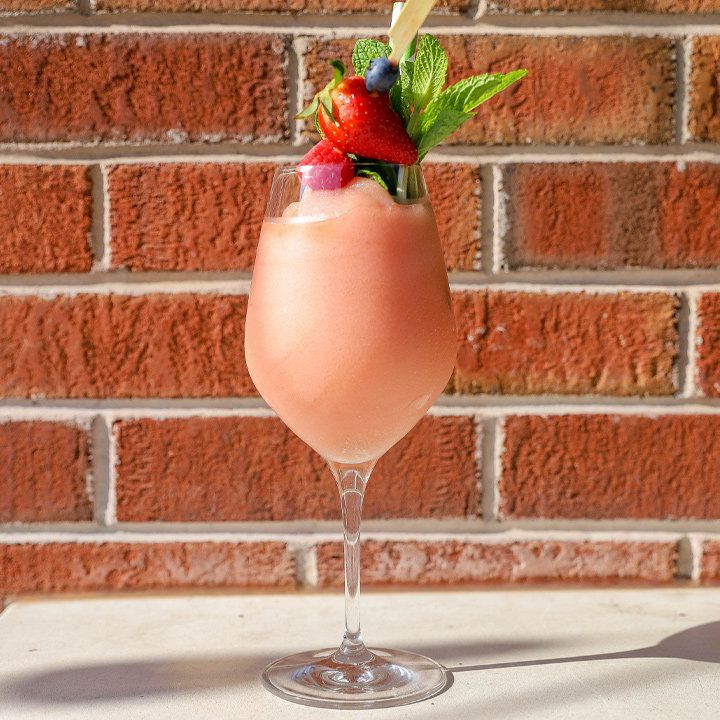 A large wine glass filled with vivid pink frosé is topped with bright berries and a verdant bunch of mint. The glass is set against a brick wall, and the shadow of its stem extends against a pale stone surface.