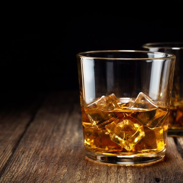 Two glass of whiskey with ice on wooden table