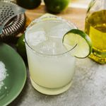 A Margarita in a salt-rimmed rocks glass garnished with a lime wheel