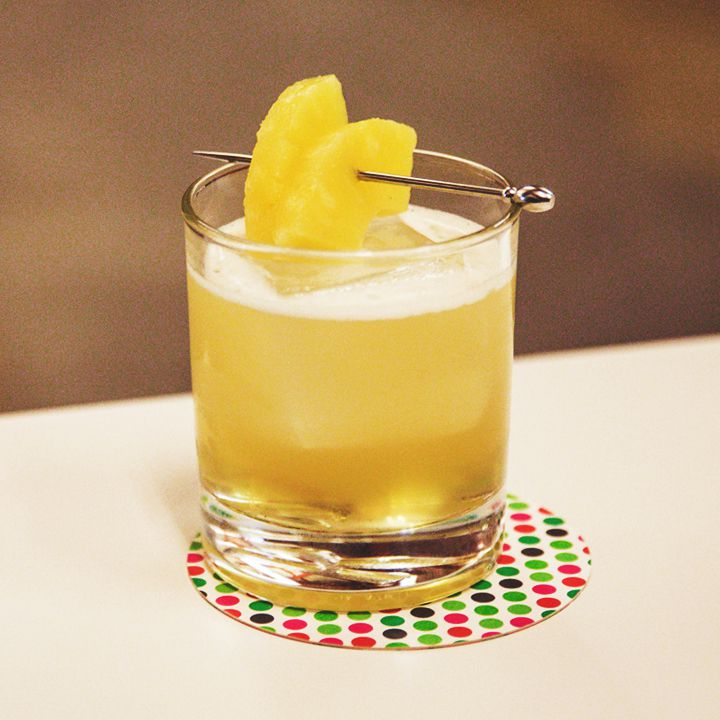 A shaken yellow-hued cocktail in a rocks glass garnished with two manicured slices of pineapple