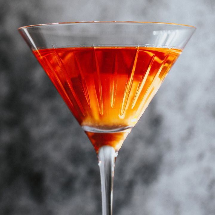 Red-orange El Presidente cocktail in a stemmed glass