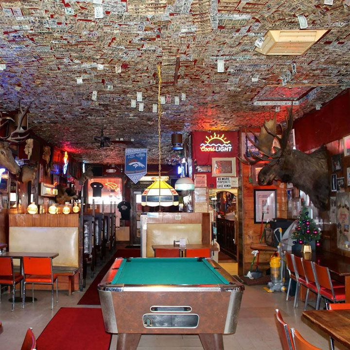 Shooting Star Saloon. The ceiling is covered in dollars bills and a pool table anchors the center of the small space