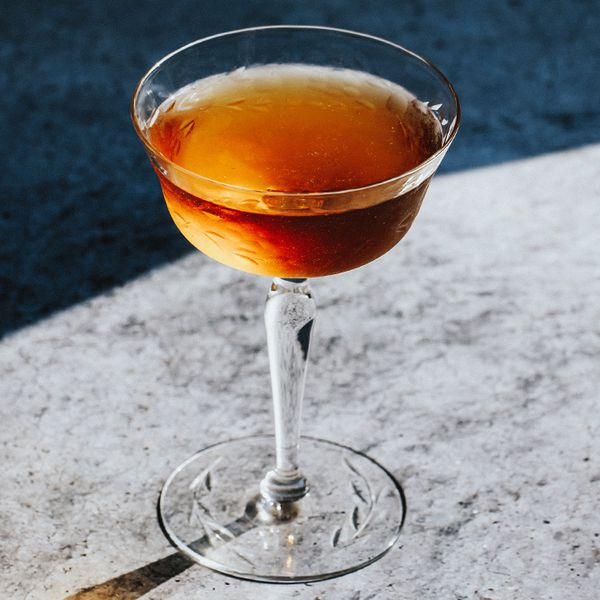 amber-colored Cooperstown cocktail in a cocktail glass, served on a gray granite surface