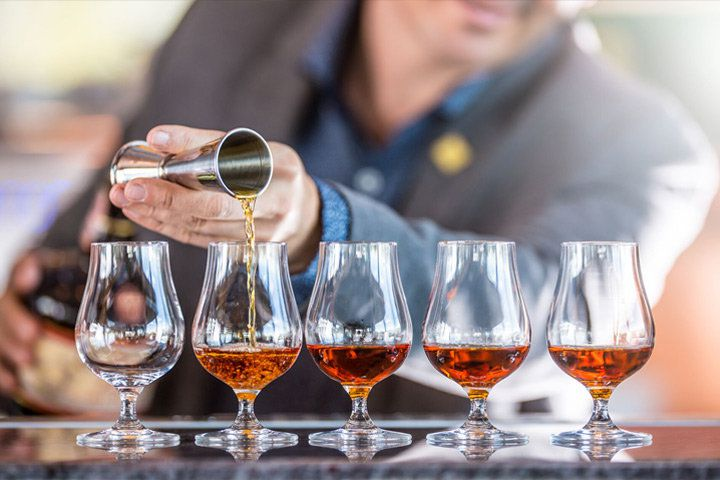 A bartender pouring Armagnac into a row of tasting glasses from a jigger
