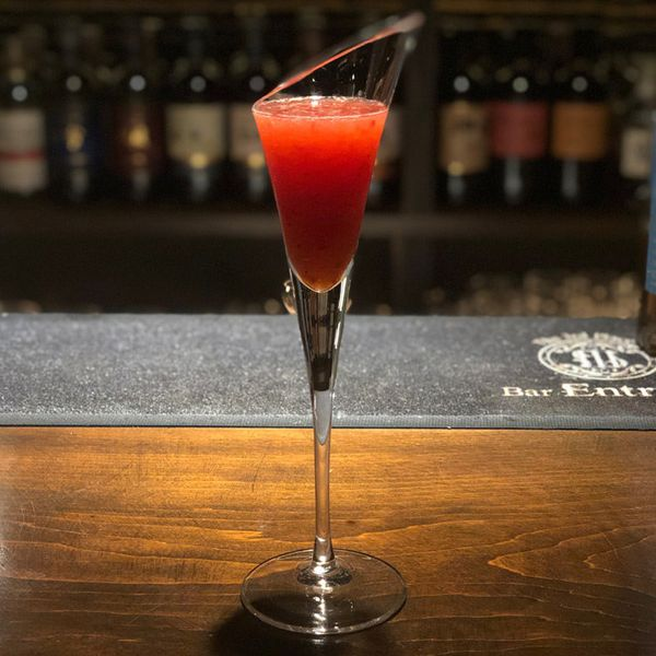 """A tall, narrow and oddly shaped cocktail glass that resembles a flute sits on a wooden bar top. It's filled with a crimson drink, and a bar mat behind it reads """"Bar Entrust"""""""