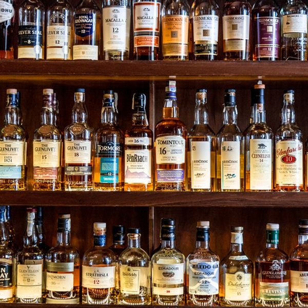 A selection of different malt Scotch whisky bottles on wooden shelves at a bar in London, UK.