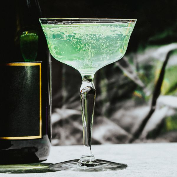 Green, bubbly Death in the Afternoon cocktail beside a champagne bottle