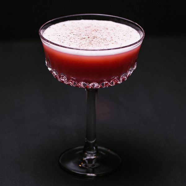 A deep-red Millionaire cocktail in a coupe glass with a grated nutmeg garnish.