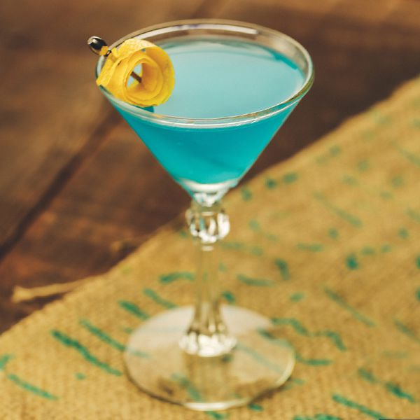 blue-colored Corpse Reviver No. Blue in a cocktail glass with a rolled up lemon twist on a metal skewer, served on a burlap placemat