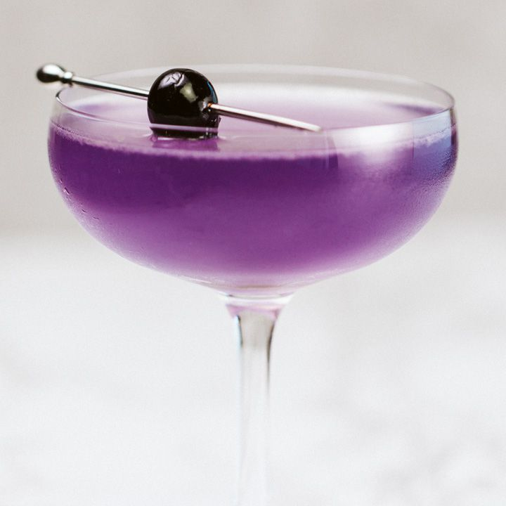 A vividly purple Aviation in a delicate coupe glass is garnished with a dark cherry, pierced on a silver pick