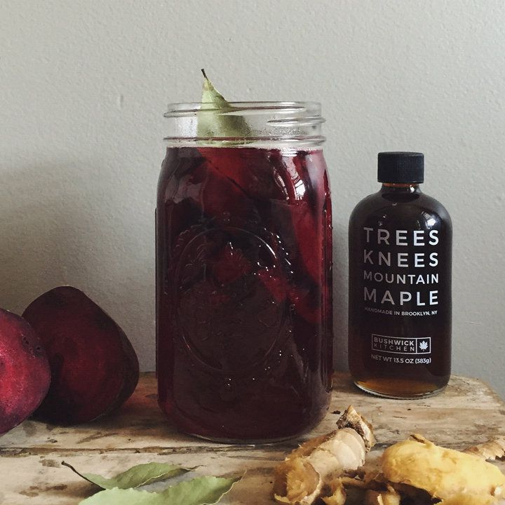 On a rough wooden cutting board, a quart-sized mason jar holds a dark red liquid, as a dry bay leaf sticks out of the open top. A halved beet rets to the left of the jar, bay leaves and ginger in front of it, and to the right a stopped bottled reads Trees Knees Mountain Maple.