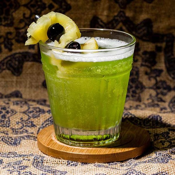 green-colored pearl harbor cocktail with skewered pineapple-and-cherry garnish, served on a wooden coaster