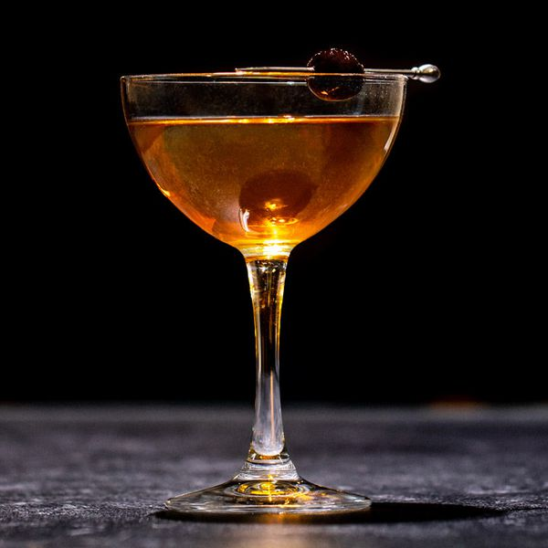Tootsie Roll cocktail in a coupe, with a skewered cherry garnish balanced on the rim