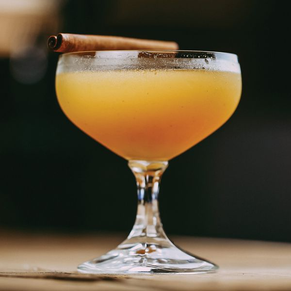 orange-hued comrade cocktail in a short-stemmed coupe glass, garnished with a cinnamon stick balanced on the rim