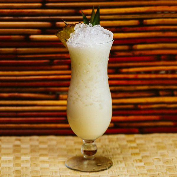 A tall and shapely glass full of crushed ice and creamy off-white Piña Colada stands on a wicker floor. Behind it, dark wood lines frame its curved shape