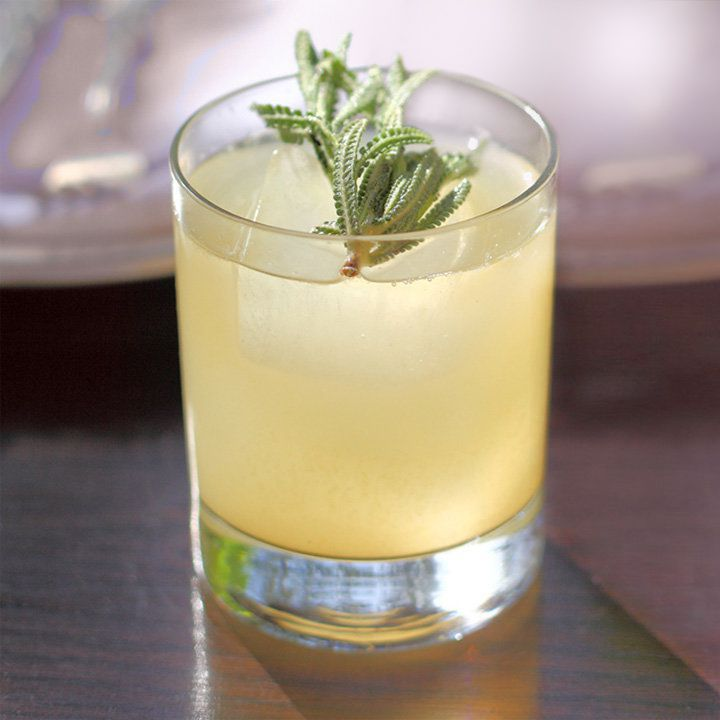 light-yellow Coal Miner's Daughter cocktail in a rocks glass with a single ice cube and lavender garnish