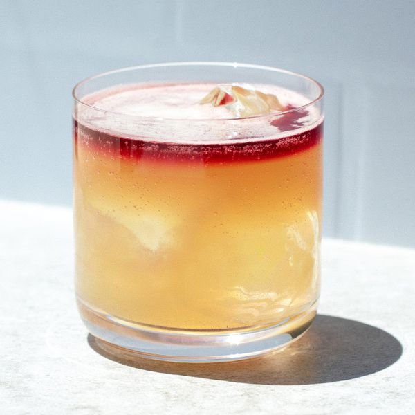 Port New York Sour in a double rocks glass with a float of tawny port layered on top, served on a white countertop