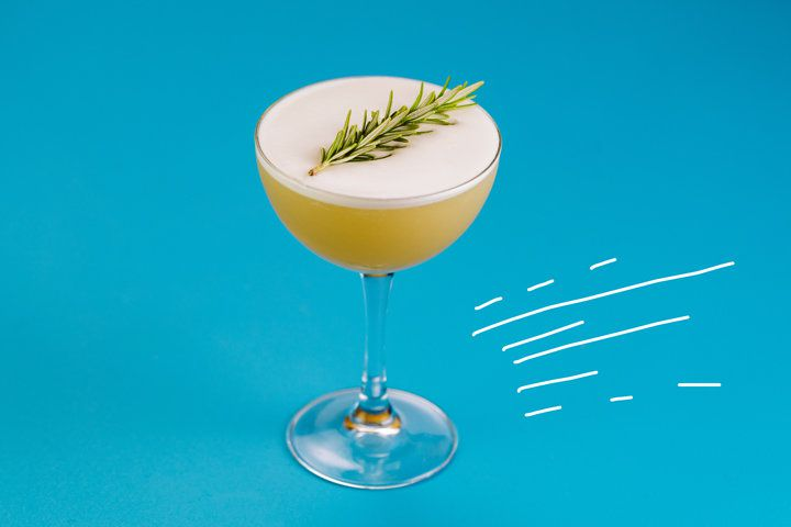 A soft yellow tequila sour served in a classic coupe and garnished with a sprig of rosemary