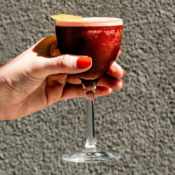 A hand with red fingernails holds a Nick & Nora glass against a stone wall. The drink within is crimson and opaque.