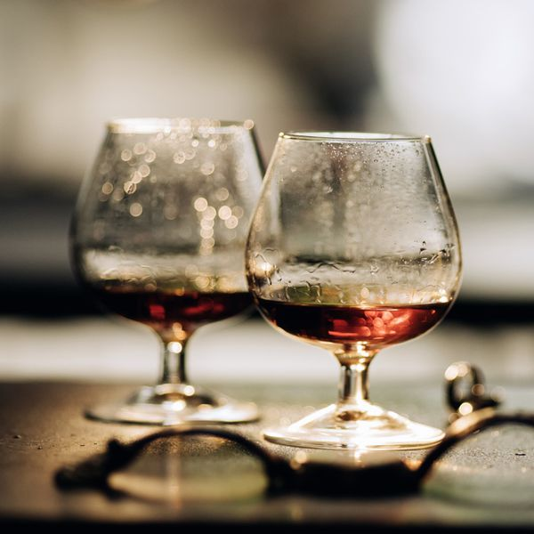 Two snifters of cognac pictures on a dark surface with a watch and ring scattered around.