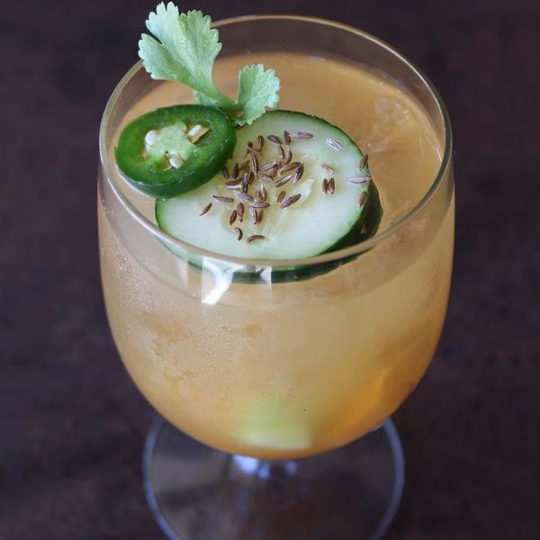 A stemmed glass is filled with an orange hued drink. It's topped with a slice of cucumber dotted with cumin seeds, a jalapeno ring, and a leaf of parsley.