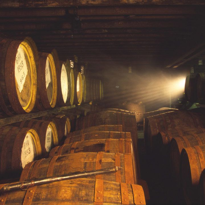 Bunnahabhain Distillery and a barrel room with slight light and oodles of aging barrels