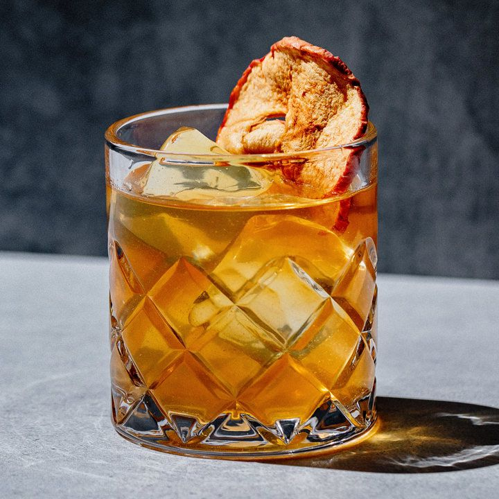 An etched rocks glass filled with an amber-hued cocktail on ice and garnished with a dried red apple slice; drink is set atop a light gray surface and is pictured against a dark gray background