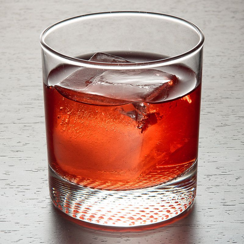 A plain rocks glass holds a large ice cube floating in a vivid red-orange cocktail. The background is a pale gray with darker lines of gray throughout.
