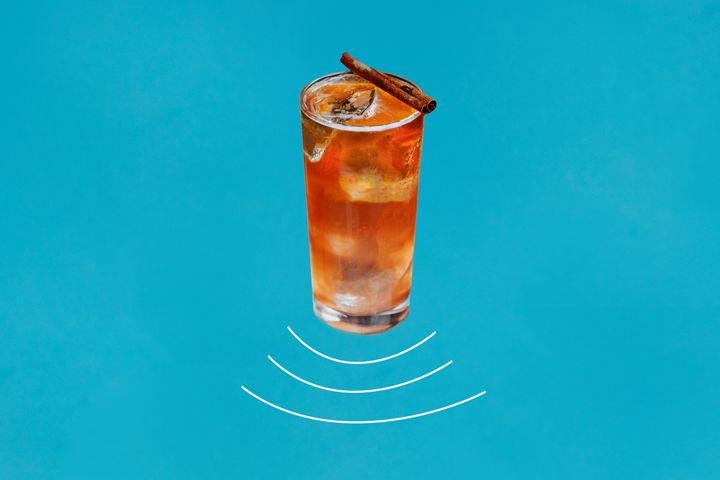 On a blue background, a tall collins glass is filled with eye and a spritzy red highball. A cinnamon stick rests on the lip of the glass