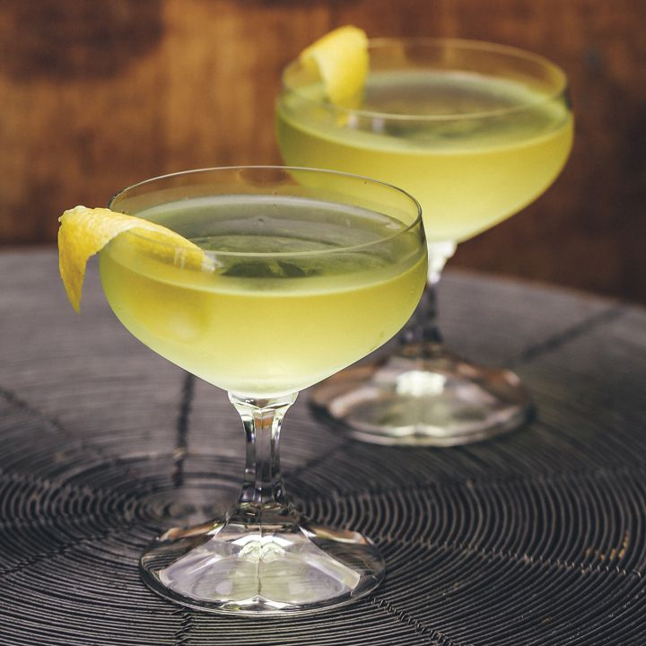 Two short stemmed coupes hold a pair of light gold cocktails. A lemon peels drapes over each glass, and they rest on a placemat of concentric rings that resembles a cross section of a tree.