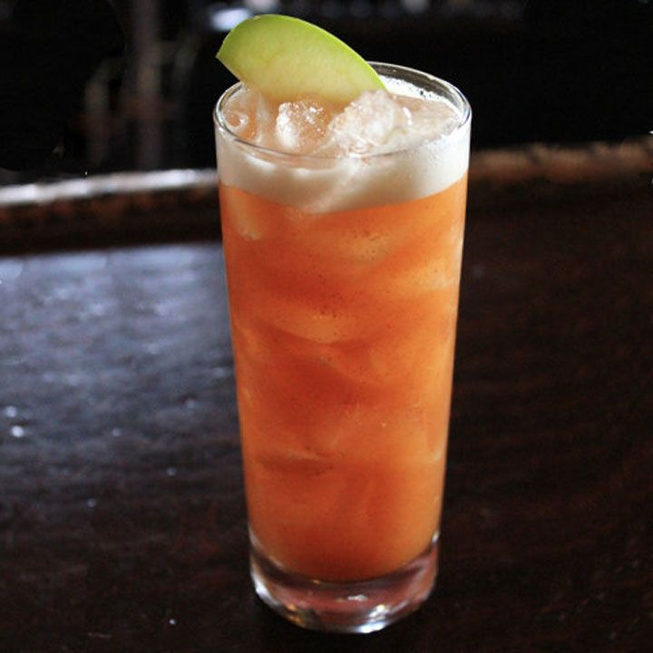 A tall highball glass rests on a dark wood bar. It's filled with ice and a red-orange drink, and garnished with a green apple slice.