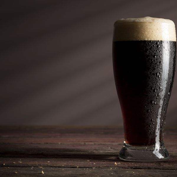 A glass of cold dark beer with foam placed on a rustic wooden table.
