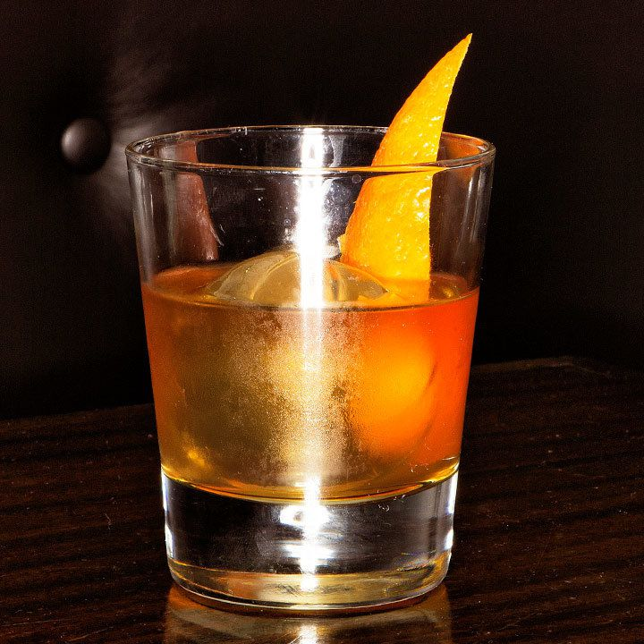orange-hued Brother's Keeper cocktail in a rocks glass with one spherical ice cube and an orange peel garnish