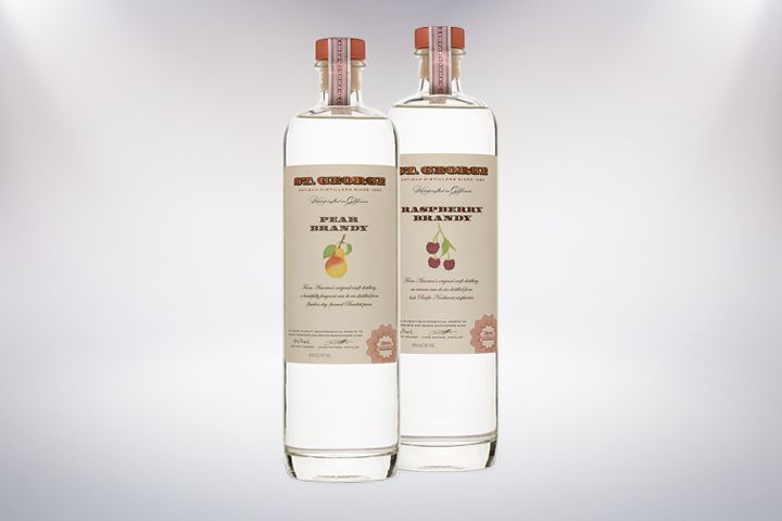 Two bottles from St George Spirits stand side-by-side on a blank background. The left bottle reads Pear Brandy, the one on the right reads Raspberry Brandy.