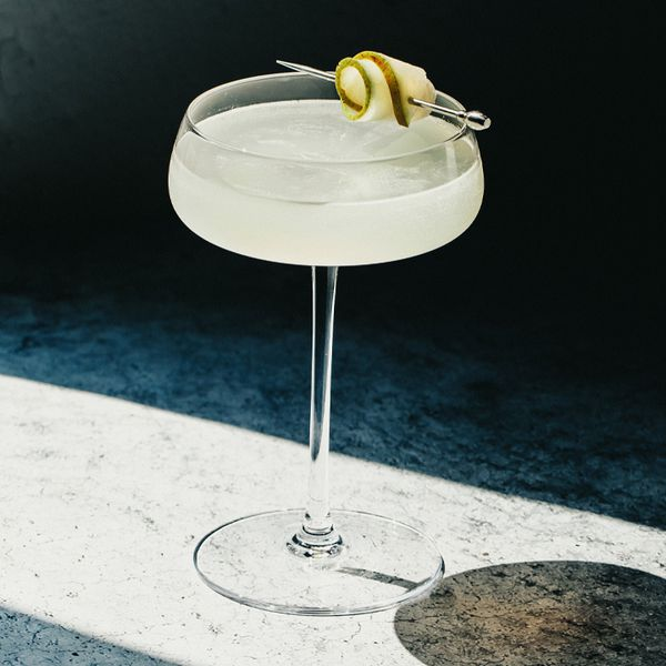 A dramatically lit photo shows a tall, flat coupe on a gray surface with a singe beam of light cutting through shadow. The glass holds a very pale yellow drink and a pear slice skewered on a silver pick.