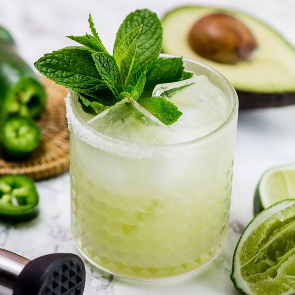 A margarita with a large sprig of fresh mint is centered in the photo on a marble slab. It is surrounded by green: limes, jalapeños and avocado.