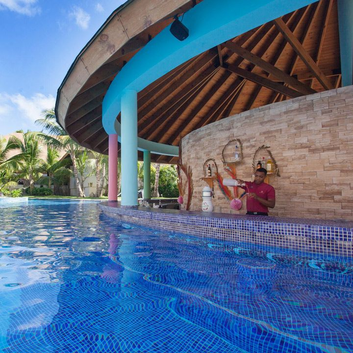 Majestic Colonial Punta Cana swim-up bar. A bartender pours a drink from behind a tiled bar jutting from the pool