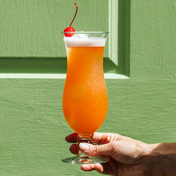hand holding a rum punch cocktail in front of a green background