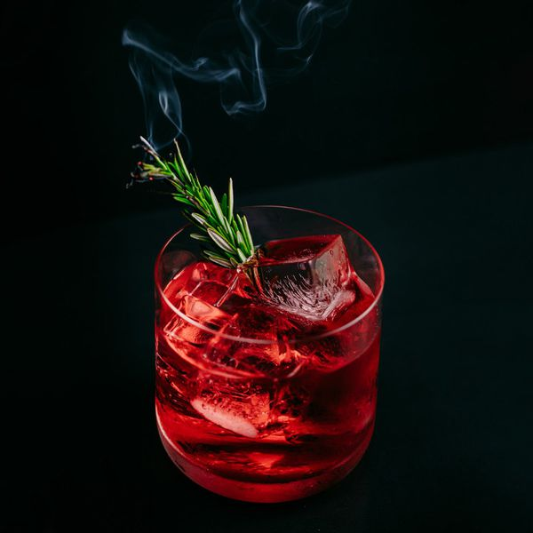 red-colored Rosemary Mezcal Negroni cocktail in a rocks glass, garnished with a lit rosemary sprig releasing a wisp of smoke
