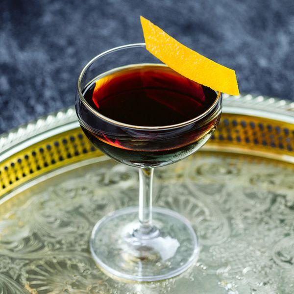 deep-brown Downhill Daring cocktail in a coupe glass with an orange peel on the rim, served on a round metal tray