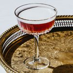 French Martini cocktail in a stemmed glass on a round gold tray