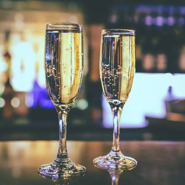 A couple of glasses of prosecco resting at the bar counter.