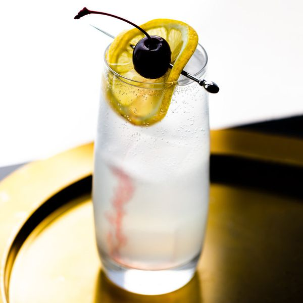 Tom Collins cocktail garnished with a lemon wheel and cherry
