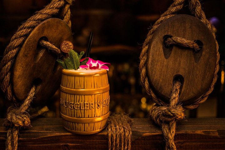 A Smuggler's Cove-branded tiki mug garnished with a flower and mint sprig set atop a wooden beam accented with rope